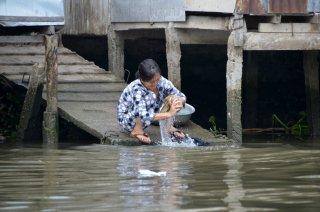 Mekong Delta, eine Frau wäscht Kleider